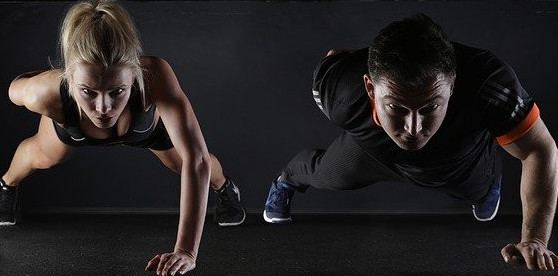 image of a man and a woman doing one arm pushups